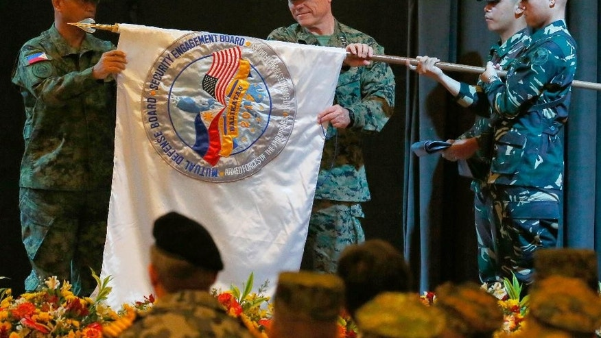 "Lt. Gen. Oscar Lactao, left, and Lt.Gen. Lawrence Nicholson, center, co-directors for this year's joint U.S.-Philippines military exercise dubbed ""Balikatan 2017"", unfurl the joint military exercise flag at the opening ceremony Monday, May 8, 2017 at Camp Aguinaldo in suburban Quezon city, northeast of Manila, Philippines. This year's military drill has been scaled down to humanitarian assistance and disaster response and anti-terrorism.(AP Photo/Bullit Marquez)"