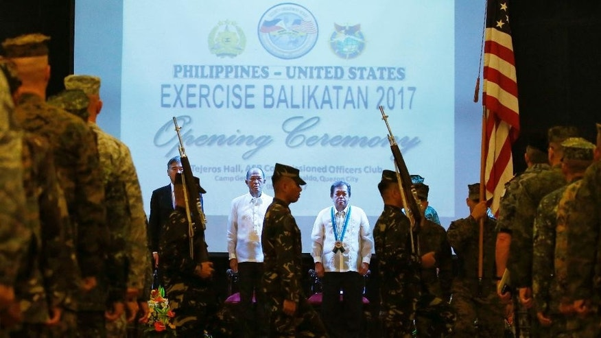 "From left to right,  U.S. Ambassador to the Philippines Sung Kim, Philippines Defense Chief Delfin Lorenzana, Undersecretary of Foreign Affairs Ariel Abadilla, stand at attention during the entry of colors at the opening ceremony for this year's joint Philippines-U.S. military exercise dubbed ""Balikatan 2017"" Monday, May 8, 2017 at Camp Aguinaldo in suburban Quezon city, northeast of Manila, Philippines.  Philippine and U.S. troops kicked off Monday their annual joint exercises that are smaller in scale than in years past, focusing on disaster response and counterterrorism while excluding territorial defense operations and maritime security.(AP Photo/Bullit Marquez)"