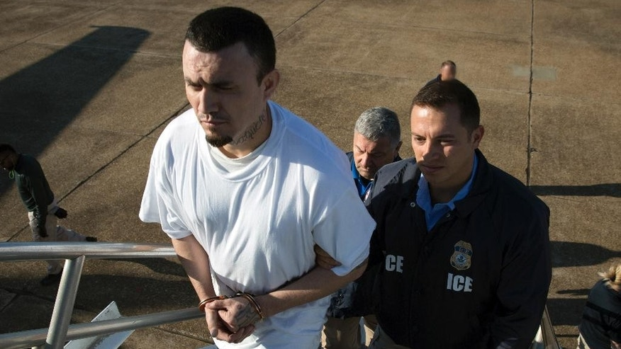 In this image provided by U.S. Immigration and Customs Enforcement, Ingmar Guandique, a documented MS-13 gang member, is escorted by ICE agents Friday, May 5, 2017, in Alexandria, La., onto a plane. Immigration and Customs Enforcement officials said May 8, that Guandique was flown Friday to San Salvador and transferred to authorities there. Officials said Guandique has been in ICE custody since June.  (Charles Reed/U.S. Immigration and Customs Enforcement via AP)