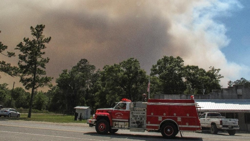 A fire truck passes as a plume of smoke rising from a wildfire burning, Monday, May 8, 2017, just outside the town of St. George, Ga. Officials placed the town under a mandatory evacuation after winds pushed the fire out of the neighboring Okefenokee National Wildlife Refuge, where a lightning strike started the blaze a month earlier. (AP Photo/Russ Bynum)
