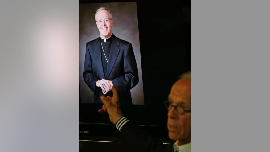 Attorney Jeff Anderson points to a photo of Bishop Michael Hoeppner of Crookston, Minn., during a news conference Tuesday, May 9, 2017 in St. Paul, Minn., where he announced a lawsuit against the bishop and diocese of concealing a report of abuse and threatening retaliation against Ron Vasek if he went public. (AP Photo/Jim Mone)