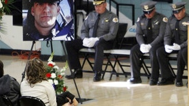 FILE - This Nov. 1, 2014 file photo shows a portrait of Santa Fe County Sheriff's Deputy Jeremy Martin during his memorial service at the Capital High School gymnasium in Santa fe, N.M. The ex-deputy accused of killing his partner in 2014 following what authorities have said was an alcohol-fueled argument will be tried again after jurors failed to reach a unanimous verdict the first time. Tai Chan's retrial in the shooting death of Martin is scheduled to begin Monday, May 8, 2017, in Las Cruces. (Luis Sanchez Saturno/The Santa Fe New Mexican via AP, File)