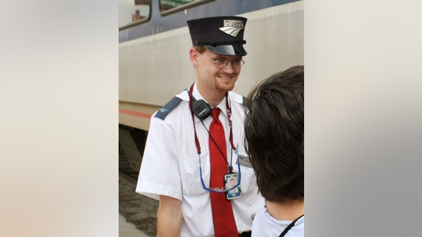 In this Aug. 21, 2007 photo, Amtrak assistant conductor, Brandon Bostian stands by as passengers board a train at the Amtrak station in St. Louis. Federal investigators have determined that an Amtrak train that crashed in Philadelphia on Tuesday, May 12, 2015, killing at least seven people, was careening through the city at 106 mph before it ran off the rails along a sharp curve.  The attorney for Bostian, the engineer at the controls of the train, said Thursday,  his client has no recollection of the accident. (Huy Richard Mach/St. Louis Post-Dispatch via AP)  MANDATORY CREDIT