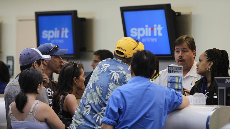 FILE - In this June 12, 2010, file photo, stranded passengers stand at the Spirit Airlines ticket counter at the Fort Lauderdale-Hollywood International Airport in Fort Lauderdale, Fla. ABC News reported on May 9, 2017, that sheriff's deputies were brought in to calm angry passengers at the airport after nine Spirit flights were cancelled on May 8. (AP Photo/Lynne Sladky, File)