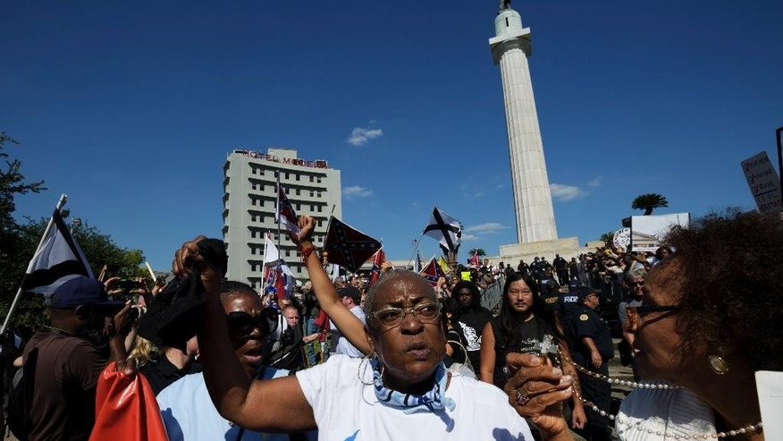 Protesters calling for the removal and the preservation of Confederate-era monuments face off in dueling demonstrations, Sunday, May 7, 2017, in New Orleans. Local media reported protesters from both sides showed up at a memorial honoring Confederate Gen. Robert E. Lee on Sunday. The statue is one of three memorials to Confederate-era figures the city plans to take down. Another memorial has already been removed. (Max Becherer/The Advocate via AP)