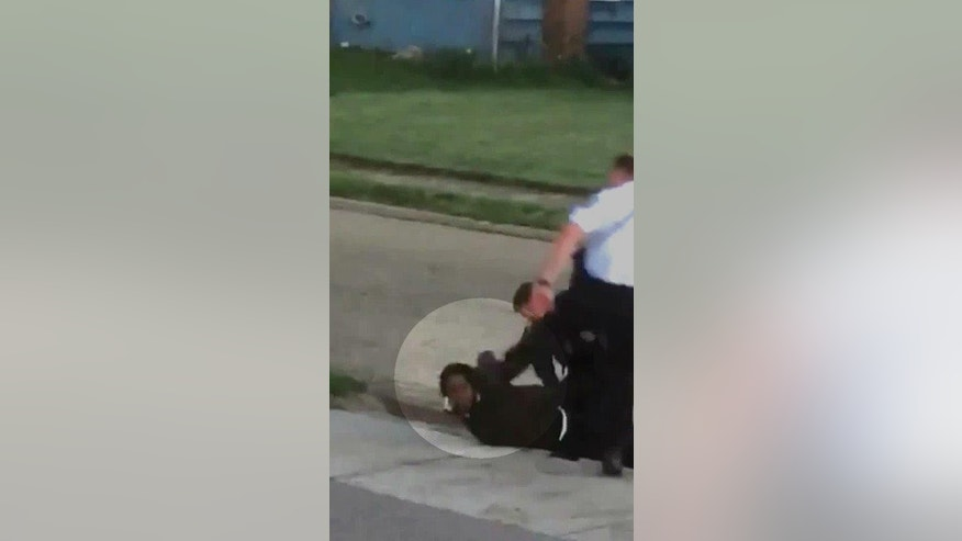 "This April 8, 2017, image made from a video and obtained from the Columbus Police Department through a records request by the Associated Press shows a Columbus officer restraining a prone man and preparing to handcuff him as a second officer appears to kick him in the head. The officer used ""unreasonable"" force that wasn't part of his training when subduing the restrained suspect in a way that appeared to show him kicking the suspect in the head, police in Ohio said Wednesday, May 10. The highlighted circle in the image was added by source. (Columbus Police Department via AP)"