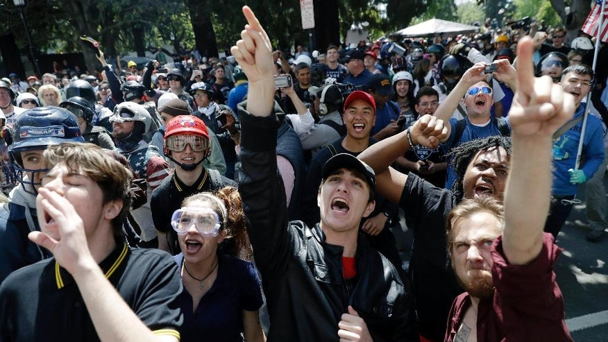 FILE - In this Thursday, April 27, 2017 file photo, demonstrators shout slogans directed at city hall during a rally for free speech near the University of California, Berkeley campus in Berkeley, Calif. Ann Coulter's speech that day was cancelled amid threats of violence, the latest example of a speaker with controversial views being blocked from talking. Since the beginning of 2016, more than two dozen campus speeches have been derailed amid controversy, according to the Foundation For Individual Rights In Education, a group that monitors free speech on campuses. (AP Photo/Marcio Jose Sanchez, File)