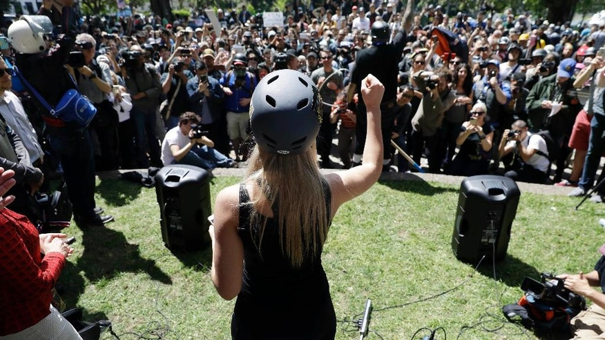 FILE - In this April 27, 2017, file photo, Lauren Southern wears a protective helmet as she speaks during a rally for free speech near the University of California, Berkeley campus in Berkeley, Calif. Demonstrators gathered to show support for free speech, while others condemned the views of Ann Coulter and her supporters. Coulter's speech was cancelled. Since the beginning of 2016, more than two dozen campus speeches have been derailed amid controversy, according to the Foundation For Individual Rights In Education, a group that monitors free speech on campuses. (AP Photo/Marcio Jose Sanchez, File)