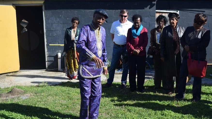"In this Feb. 11, 2017 photo, Dr. Thomas J. Durant Jr., center, Professor Emeritus of African-American Studies at Louisiana State University, performs a libation ceremony on the grounds of American Legion Raymond Stafford Post 513 in Thibodaux, La. Victims of the 1887 Thibodaux Massacre are believed buried in a mass grave at the site. This memorial, conducted in conjunction with the River Road African-American Museum in Donaldsonville, is one of several commemorations held since publication of ""The Thibodaux Massacre: Racial Violence and the 1887 Sugar Cane Labor Strike"" by John DeSantis  (James Loiselle/Courtesy of John DeSantis via AP)"