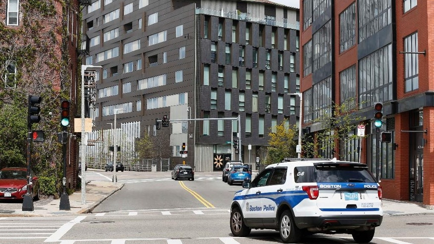 A Boston police vehicle patrols, Monday, May 8, 2017, near the scene of a double murder in the penthouse of the Macallen Building, center, in Boston. Bampumim Teixeira is charged with killing Dr. Lina Bolanos and Dr. Richard Field on Friday night  at the Macallen Building. (AP Photo/Michael Dwyer)