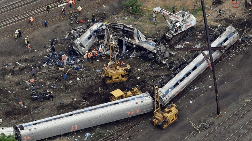 FILE – In this May 13, 2015, file photo, emergency personnel work near the wreckage of a New York City-bound Amtrak passenger train following a derailment that killed eight people and injured about 200 others in Philadelphia. The state's attorney general has a wide range of options in responding to a judge's order to arrest a speeding Amtrak engineer involved in the deadly 2015 crash, a law professor said Friday, May 12, 2017. (AP Photo/Patrick Semansky, File)