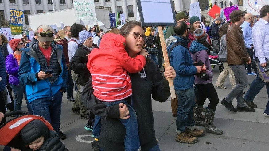 "In this Saturday, April 22, 2017 photo, Katie Farnan carries her 3-year-old son, Leo, as they join protesters in the March for Science as it passes by the City/County Building in downtown Denver. She volunteered for Obama's re-election campaign in 2012, but didn't do the same for Hillary Clinton's presidential run last year. She had two young kids. Plus, she added, ""I thought it was in the bag."" (AP Photo/Nick Riccardi)"