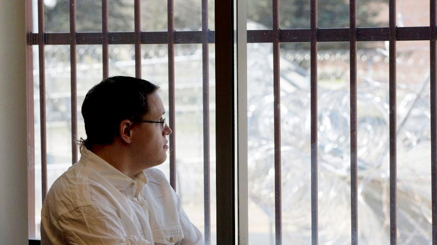 Christopher Lee looks through a window secured by bars towards a barbed wire fence surrounding the building from a conference room at the Minnesota Sex Offender Program in St. Peter, Minn., on March 28, 2017. Lee has been in the program since 2005, four days before he turned 19. An ongoing Associated Press investigation has documented how K-12 schools in the United States can fail to protect students in their care from sexual assault, sometimes minimizing or even covering up incidents. Schools also struggle to help sexually aggressive students, both before and after they do lasting harm. (AP Photo/Jim Mone)