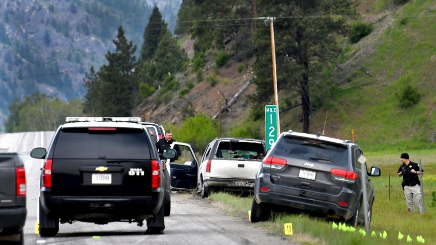 Law enforcement personnel investigate the scene of a shootout on Interstate 90 east of Missoula following a high-speed chase Tuesday, May 16, 2017. The white SUV was the vehicle being pursued. The driver of the SUV has been arrested and a passenger was shot by law enforcement and taken to the hospital.  (Kurt Wilson/The Missoulian via AP)