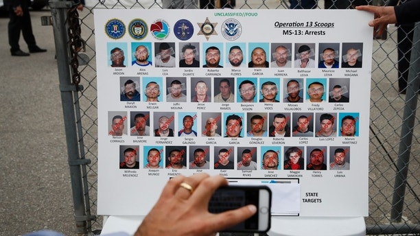 A reporter uses his smartphone to photograph a board showing images of MS-13 gang members during a news conference Wednesday, May 17, 2017, in Los Angeles. Hundreds of federal and local law enforcement fanned out across Los Angeles, serving arrest and search warrants as part of a three-year investigation into the violent and brutal street gang MS-13. (AP Photo/Jae C. Hong)