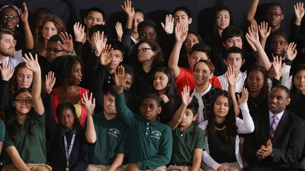 ADELPHI, MD - FEBRUARY 04:  Students raise their hands when asked if they plan on going to college before the arrival of U.S. President Barack Obama at Buck Lodge Middle School February 4, 2014 in Adelphi, Maryland. As part of the president's ConnectED program, Obama has tasked the Federal Communications Commission to help to build high-speed digital connections to America's schools and libraries, with the goal of getting 99-percent of American students to next-generation broadband and wireless technology within five years.  (Photo by Chip Somodevilla/Getty Images)