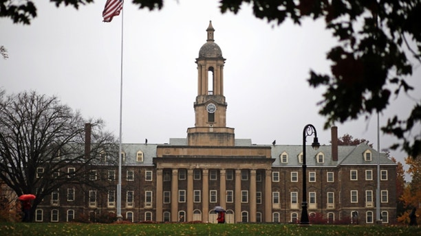 A Penn State student walks in the rain past Old Main on the Penn State main campus in State College, Pa., Wednesday, Oct. 28, 2015. (AP Photo/Gene J. Puskar)