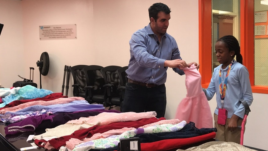 Sam Sisakhti, the founder of Us Trendy, with many of the donated dresses.