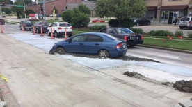 In this Wednesday, May 24, 2017 photo, a car driven by a 19-year-old driver is stuck in the newly poured concrete in Lincoln, Neb. A police incident report says it wasn't obvious that the concrete wasn't dry and that driver drove into it through a 24-foot (7-meter) gap between traffic control cones. City engineer Thomas Shafer says the driver is responsible for the repairs and could face about a $10,000 bill for the repairs. (Mike Palm, The City of Lincoln Public Works and Utilities Department via AP)