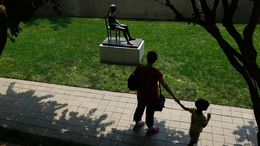 A woman and child walk through the Smithsonian Institution's Hirshhorn Sculpture Garden in Washington June 6, 2012.