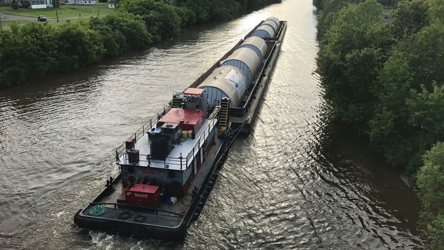 In this undated photo, a barge carrying Chinese-made beer fermentation tanks floats down the Erie Canal in Clyde, N.Y., toward the Genesee Brewery in Rochester, N.Y. Some politicians are irritated that the Rochester brewery, which receives state economic development funding, bought beer fermentation tanks from China that could have been produced in New York. (Michael Riviello via AP)
