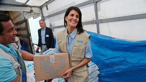 "FILE - In this May 24, 2017, file photo, U.S. Ambassador to the U.N. Nikki Haley holds a food parcel provided by the World Food Programme, part of the humanitarian aid shipments into Syria, during a visit at the Reyhanli border crossing with Syria, near Hatay, southern Turkey. Haley is presenting another side of President Donald Trump's ""America First"" doctrine, one that focuses on human rights and humanitarian assistance. (AP Photo/Burhan Ozbilici, Pool)"