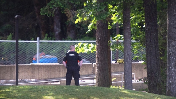 "An Evergreen State College police officers keeps watch over campus as student evacuate following a ""direct threat"" on Thursday, June 1, 2017.  The announcement posted on the school's website Thursday asked everyone to leave the Olympia campus or return to residence halls for further instructions. The post did not provide other details. (Tony Overman /The Olympian via AP)"