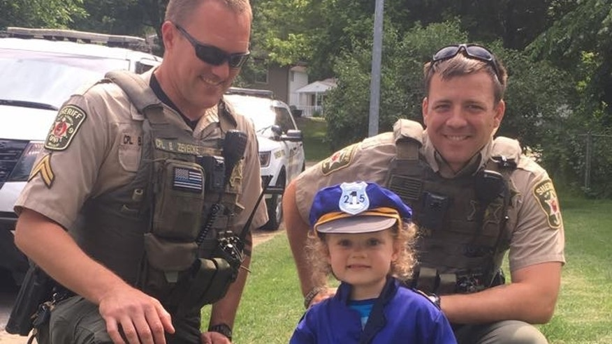 Kansas City police officers posing with Hannah Pasley in her new uniform.