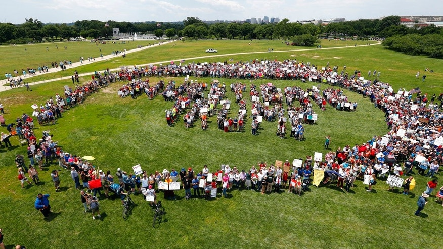"Protesters form letters that spell ""Impeach Trump"" at a rally to protest President Trump and his policies on the National Mall June 3."
