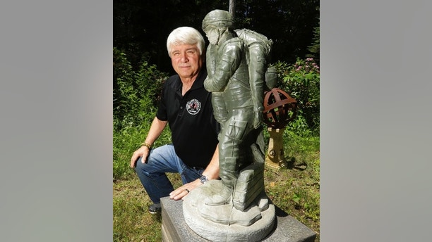 In a photo from Friday, June 9, 2017, former Army medic James McCloughan kneels next to a statue presented to him by a fellow soldier in South Haven, Mich.  An Army spokeswoman said Tuesday, June 13 that McCloughan, who saved the lives of 10 soldiers during the Battle of Nui Yon Hill in May 1969 in Vietnam, will become the first person to be awarded the nation's highest military honor by President Donald Trump. (AP Photo/Carlos Osorio)