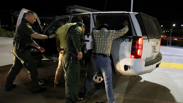 U.S. border patrol agents detain two men from India after they entered the United States by climbing over the border wall from Mexico in Calexico, California, U.S. February 8, 2017. Picture taken February 8, 2017.  REUTERS/Mike Blake - RTX30D0H