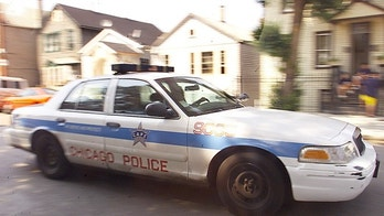 A Chicago police department cruiser rides past the house where a
