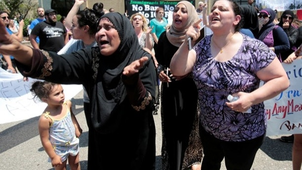 A group of women react as they talk about family members seized on Sunday by Immigration and Customs Enforcement agents during a rally outside the Mother of God Catholic Chaldean church in Southfield, Michigan, U.S., June 12, 2017.   REUTERS/Rebecca Cook - RTS16RX7