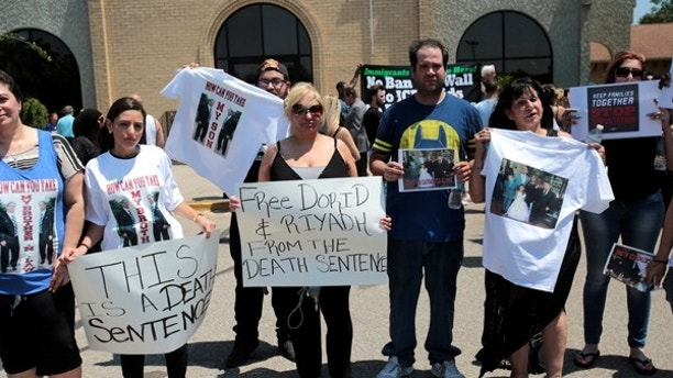 Chaldean-American Nadia Al-Raviah (C) stands with family members protesting against the seizure of her husband and brother Sunday by Immigration and Customs Enforcement agents during a rally outside the Mother of God Chaldean church in Southfield, Michigan, U.S., June 12, 2017.   REUTERS/Rebecca Cook - RTS16RRH