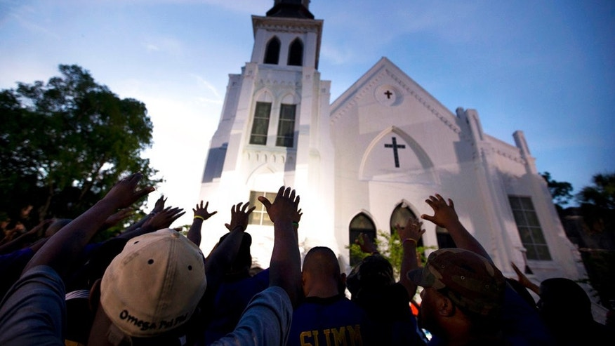 The men of Omega Psi Phi fraternity lead a crowd of people in prayer outside the Emanuel AME Church, after a memorial for the nine people killed by Dylann Roof in Charleston, S.C. June 17, 2017. (AP Photo/Stephen B. Morton)