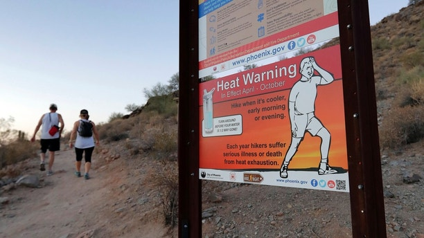 A sign warns hikers about severe heat as they begin their hike at sunrise to avoid the excessive heat, Friday, June 16, 2017, in Phoenix. A record heat wave is rolling into Arizona, Nevada and California, threatening to bring 120-degree temperatures to Phoenix by early next week. (AP Photo/Matt York)