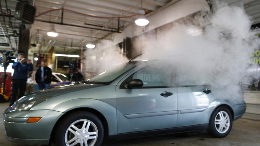 In this April 16, 2015 file photo, smoke created by water vapor billows out of the windows of a car, used by Colorado to fight stoned driving with youth demographics, during a demonstration by the Colorado Department of Transportation in southeast Denver.