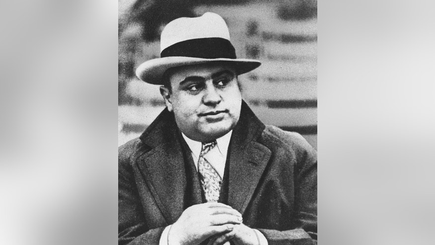 "FILE - In this Jan. 19, 1931 file photograph, Chicago mobster Al Capone is seen at a football game in Chicago. Artifacts connected to some of the nation's most notorious gangsters are being auctioned this weekend. A handwritten musical composition by Al Capone, a letter written by a jailed John Gotti asking someone to ""keep the martinis cold,"" and jewelry that belonged to Bonnie and Clyde are among the items up for bid Saturday in the ""Gangsters, Outlaws and Lawmen"" auction in Cambridge, Mass. (AP Photo/File)"
