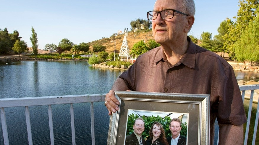 In this Friday, June 23, 2017 photo, Frank Kerrigan holds onto a photograph of his three children John, Carole, and Frank, near Wildomar, Calif. Kerrigan, who thought his son Frank had died, learned he buried the wrong man. Kerrigan said the Orange County coroner's office mistakenly identified a body found dead on May 6 as that of his son. (Andrew Foulk/The Orange County Register via AP)