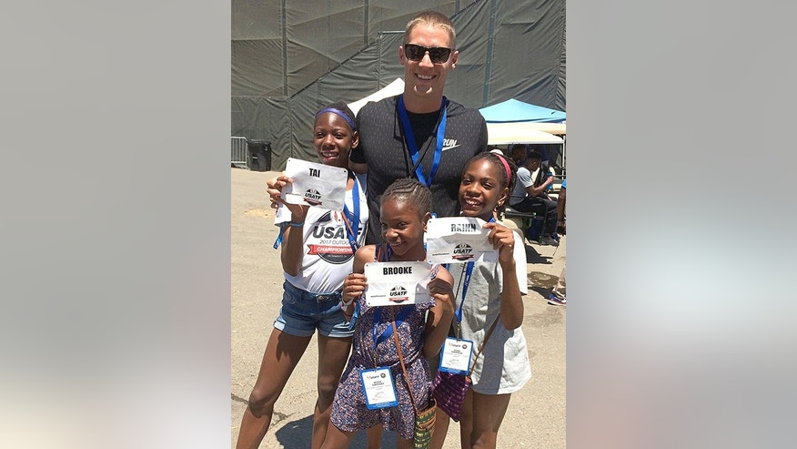 Decathlete Trey Hardee poses with the Sheppard sisters, Tai, 12, left, Brooke, 9, center and Rainn, 11, right, at the U.S. Track and Field Championships, in Sacramento, Calif.