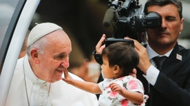 An unidentified child, who was carried out from the crowd to meet Pope Francis, reaches out to touch the Pontiff's face during a parade on his way to celebrate Sunday Mass on the Benjamin Franklin Parkway in Philadelphia, Sunday, Sept. 27, 2015. Pope Francis is in Philadelphia for the last leg of his six-day visit to the United States. (AP Photo/Pablo Martinez Monsivais)