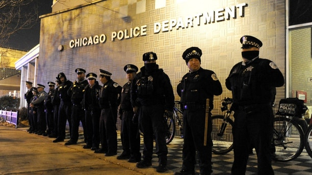 FILE - In this Nov. 24, 2015, file photo, Chicago police officers line up outside the District 1 central headquarters in Chicago, during a protest for the fatal police shooting of 17-year-old Laquan McDonald. Special prosecutor Patricia Brown-Holmes announced Tuesday, June 27, 2017, that three Chicago police officers were indicted on felony charges that they conspired to cover up the actions of Chicago Police Officer Jason Van Dyke in the killing of McDonald. The indictment, approved by a Cook County grand jury, alleges that one current and two former officers lied about the events of Oct. 20, 2014 when Van Dyke shot the black teenager 16 times. (AP Photo/Paul Beaty File)