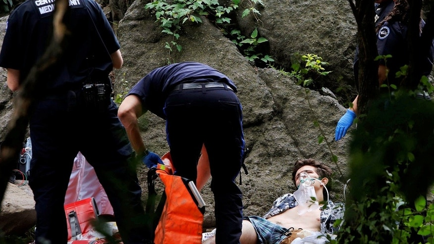 Medics stand over a man who was injured after an explosion in Central Park, in Manhattan, New York, U.S. on July 3, 2016.  REUTERS/Andrew Kelly - RTX2JIFW