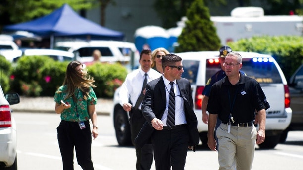 FBI Detroit spokesman Tim Wiley, center, walks over to brief the media at Bishop International Airport, Wednesday morning, June 21, 2017, in Flint, Mich. Officials evacuated the airport Wednesday, where a witness said he saw an officer bleeding from his neck and a knife nearby on the ground. Authorities say the injured officer's condition is improving. (Jake May/The Flint Journal-MLive.com via AP)