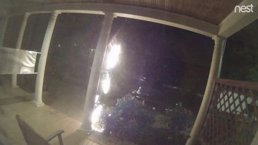 Surveillance video shows a man coming up to the front porch of a Richmond, Virginia home, pulling out a lighter, setting the American flag on fire and then walking away. (Richmond Police Department)
