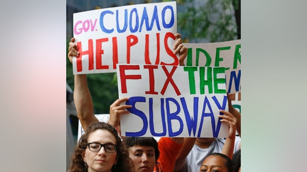 Protesters hold signs during a rush hour rally demanding better New York City subway service as they gathered outside the offices of New York Gov. Andrew Cuomo, Wednesday, June 28, 2017, in New York. Earlier this month hundreds of riders were trapped aboard a sweltering F-train, and dozens of riders were injured Tuesday in an A-train derailment in Harlem. Funding for the city's subway system comes from the state. (AP Photo/Kathy Willens)