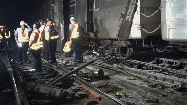 In this photo provided by the Transport Workers Union, Local 100, workers from the New York Metropolitan Transportation Authority examine damaged train tracks, at the scene of a subway derailment, Tuesday, June 27, 2017, in New York. A subway train derailed near a station in the Harlem neighborhood of New York, frightening passengers and resulting in minor injuries as hundreds of people were evacuated from trains along the subway line. (Transport Workers Union, Local 100 via AP)