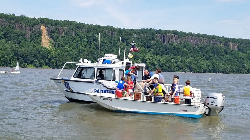 A small sailboat capsized in the Hudson River off New York City, sending children on board into the water.