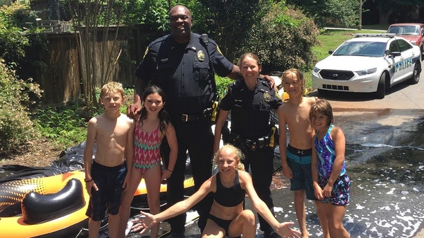 Asheville Police officers take ride on homemade water slide