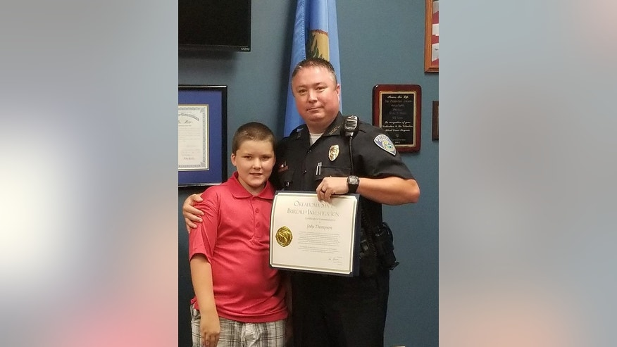 Officer Jody Thompson after receiving his certificate of commendation, posing with John.